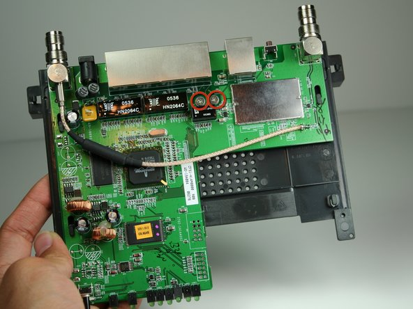 Locate the 2 M2.5x6mm screws that attach the motherboard to the back case.