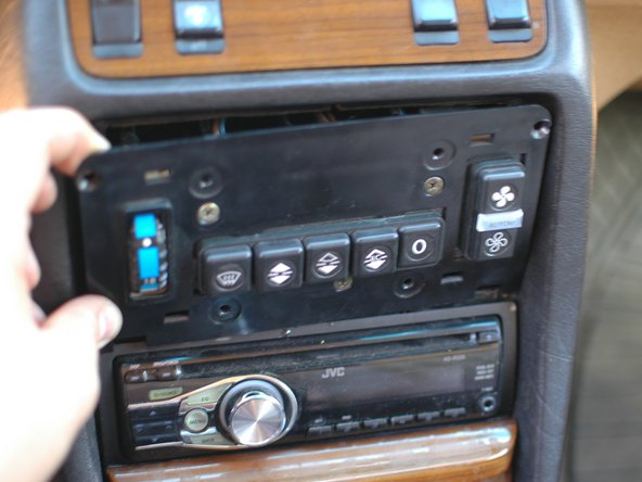 Then use a pry tool, followed by your fingers, to carefully pull the climate control unit forward from the top. The bottom is held in place by two tabs - use care not to crack them by pulling the panel too far forward.