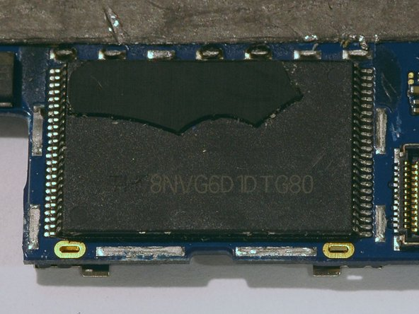 The 8GB NAND flash chip (Toshiba TH58NVG6D1DTG80), revealed after removing a soldered-down cover. This chip was covered by a plastic shield as well, which we've partially removed to see the markings beneath.