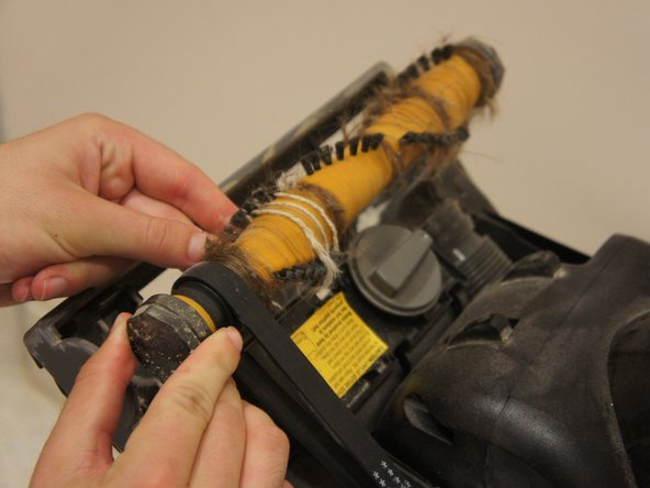 After one end is displaced, remove the other side by pressing firmly upwards from below the the brush roll.