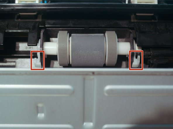 The pickup roller can now be removed by rotating the white tabs upwards and pulling them out.