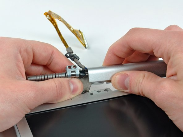 Carefully slide the display data cable out of its channel in the clutch hinges.