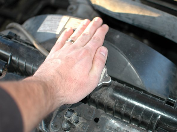 With the hood on your car up, begin by opening the radiator cap to allow the radiator to drain more efficiently.