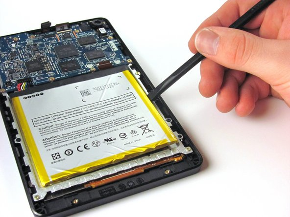 Gently pry the battery free from the adhesive holding it in place.