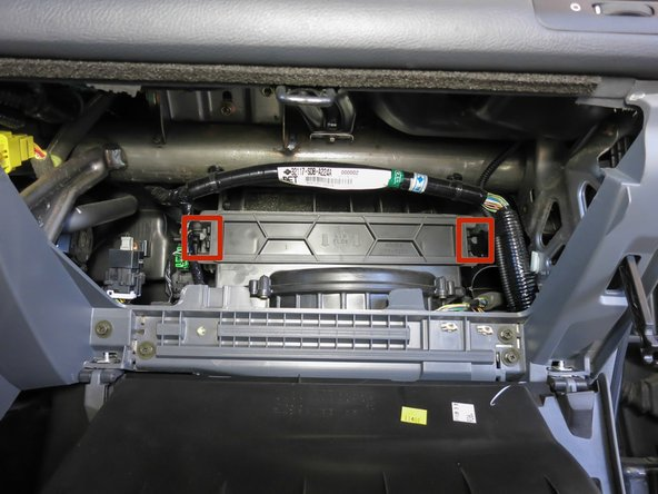 Locate the cover for the cabin air filter and notice the two tabs on either side.