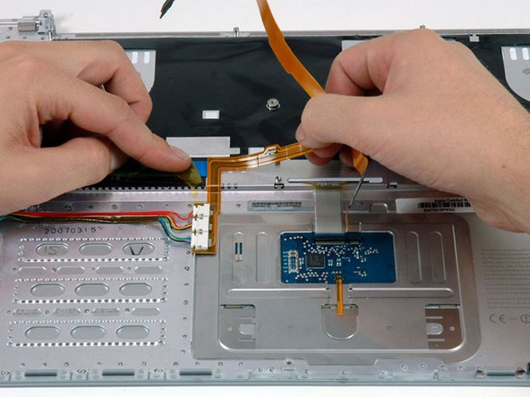 Carefully peel up the orange ribbon cable which carries the power and sleep signals, removing tape as necessary.