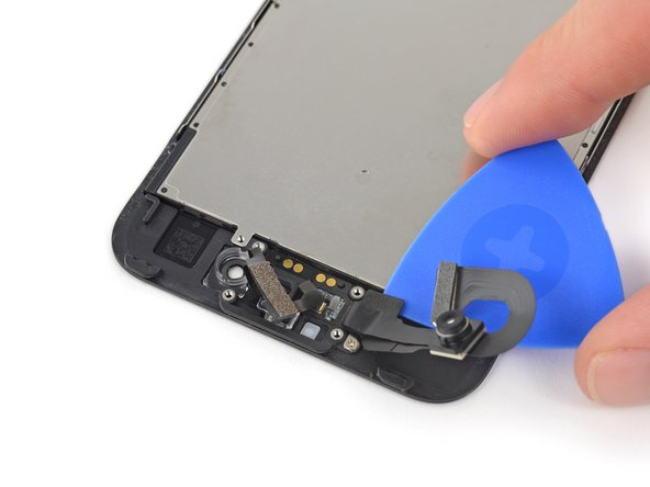 Use the pick to lift the camera cable up off of the two plastic posts on the front panel and separate it from the last of the adhesive.