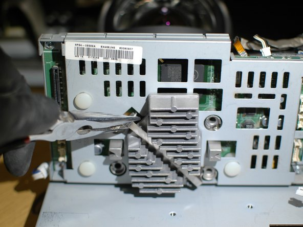 Next use a pliers to remove the clip that holds the DLP chip heatsink in place.