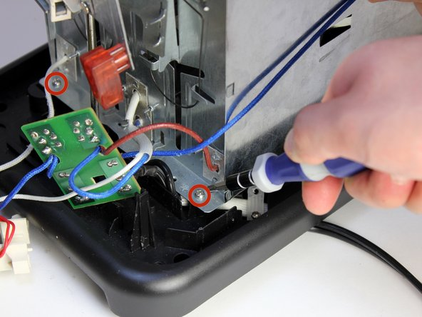 Using a Philips #2 screwdriver, remove the front two 8mm screws attaching the chassis to the base.