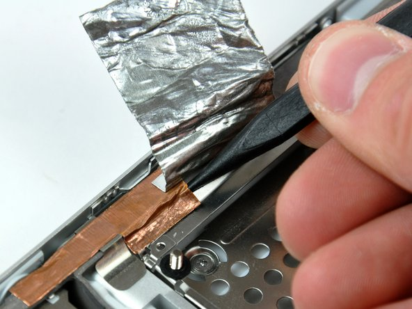 Use the tip of a spudger to peel back the small strip of copper tape off the edge of the PC card cage near the side of the lower case.