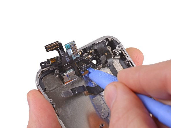 Use the edge of a plastic opening tool to pry the earpiece speaker off the adhesive securing it to the outer case. Note that the power button cable is glued to the the case as well, and will need to be pried up.
