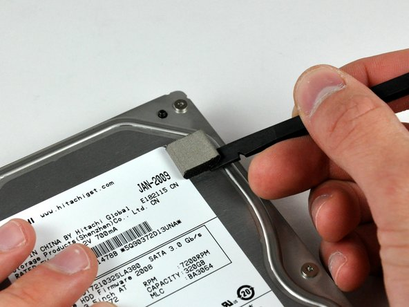 Use a spudger to remove the small piece of EMI foam from the top of the hard drive.