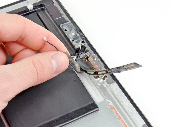 Move the dock connector/speaker cables out of the way and peel the bluetooth/wi-fi antenna cable off the adhesive securing it to the rear case.