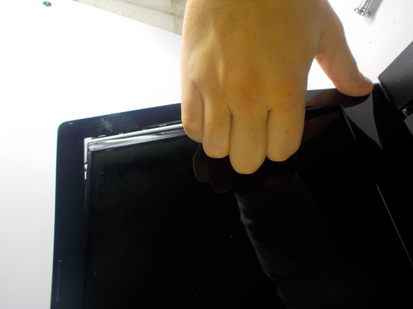 Finish removing the bezel by using your hand on the inside of the screen and popping it off.