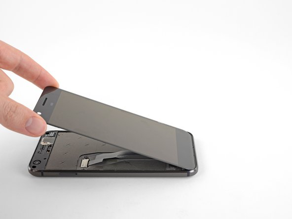 With the adhesive cut, slowly lift the display up from the top (the side with the speaker-grille cutout), carefully flip it over vertically toward the bottom of the device, and rest it on its face, as shown.