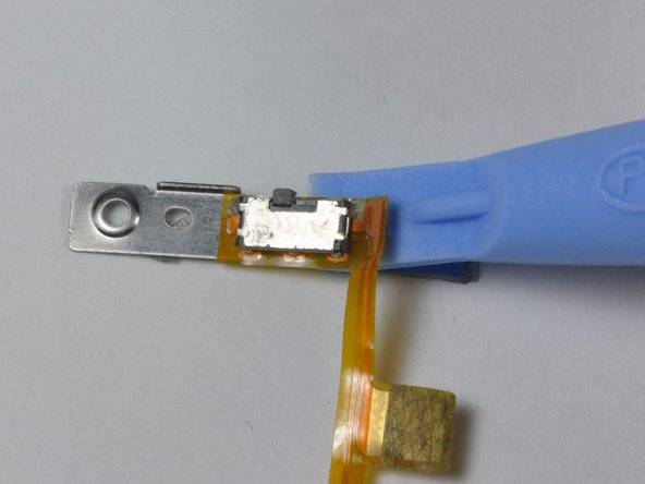 Use the small iPod opening tool to carefully peel the orange ribbon cable and attached black Hold switch up from the metal backing.