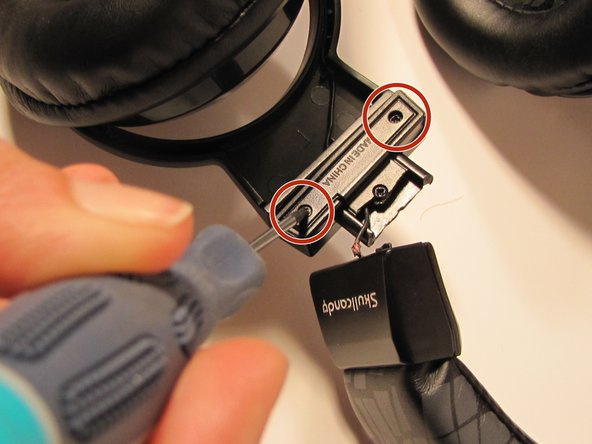 Use a Philips #0 screwdriver to remove the two 9 cm screws beneath the break. Keep them in a safe place for reassembly.