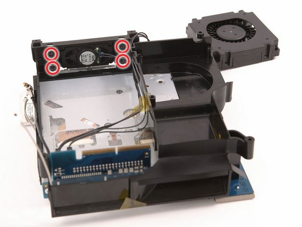 While holding the assembly with the speaker resting on the table, remove the four black Phillips screws holding the speaker in place and their associated rubber bumpers.