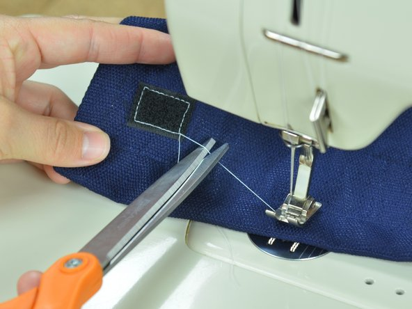 Clip the threads, freeing the fabric from the sewing machine.