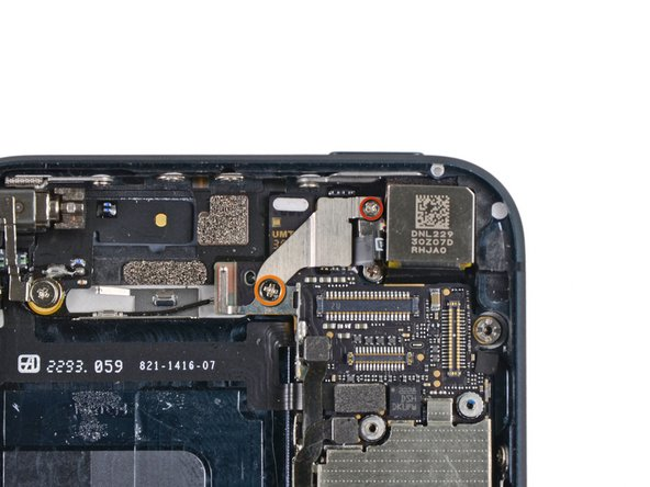Remove the following two screws securing the top logic board bracket to the rear case: