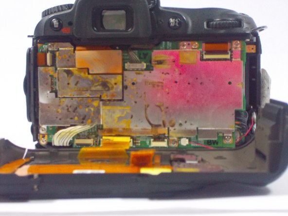 After, remove the two orange ribbon connectors attached to the interior of the camera with tweezers.