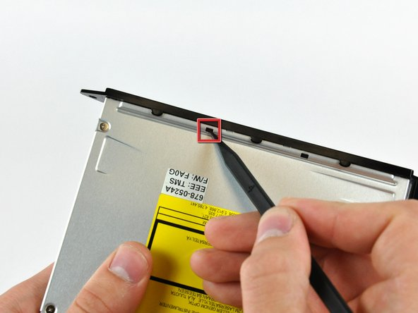 Push the two optical drive bracket tabs out of their slots in the top of the optical drive.