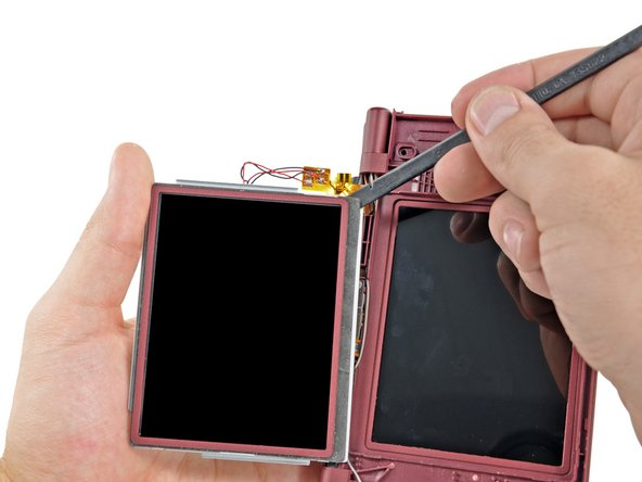 In the same manner as previously described, detach the adhesive along the right side of the upper LCD.