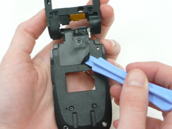 Flip the phone over and gently use iPod opening device to remove the right half of the black tape.