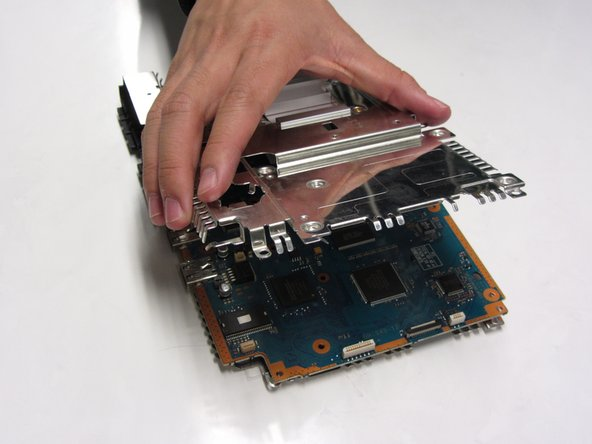 Gently lift the metal plates from both the top and bottom of the motherboard.