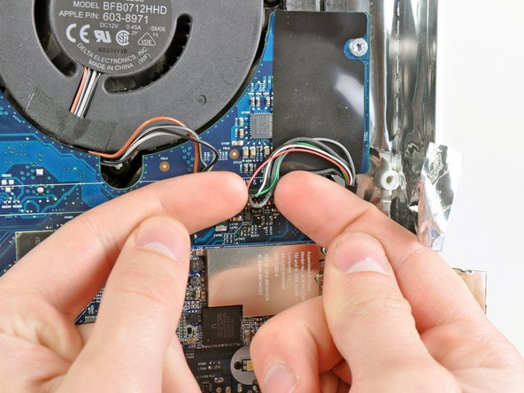 Use both fingertips to disconnect the camera and microphone cable from its socket on the logic board.