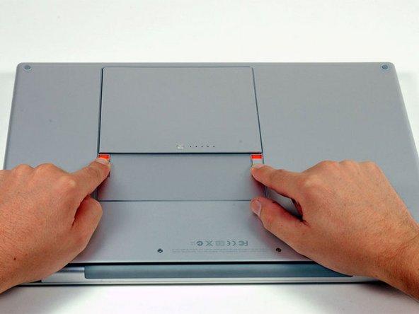 Ziehe die beiden Laschen, die den Akku im Laptop halten, mit den Fingern vom Akku weg und nimm den Akku aus dem Rechner heraus.