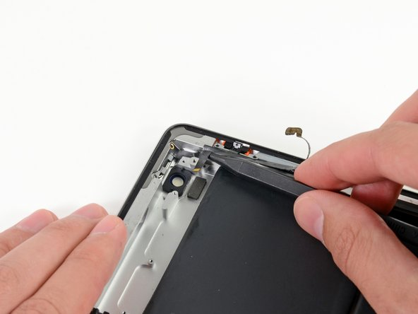 With the tip of the spudger still underneath the ribbon cable, gently lift the power button out of its socket in the aluminum frame.