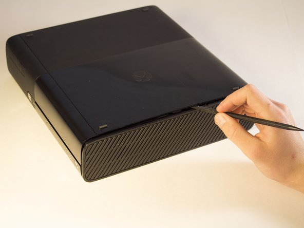 Push the Spudger into the crevice between the grated top panel of the Xbox and the bottom body with the rubber feet.