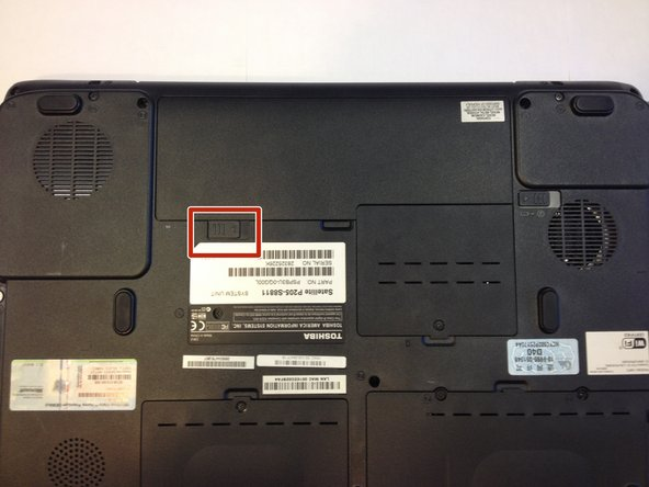 Flip the laptop over so the bottom is facing upward and the battery is on top.