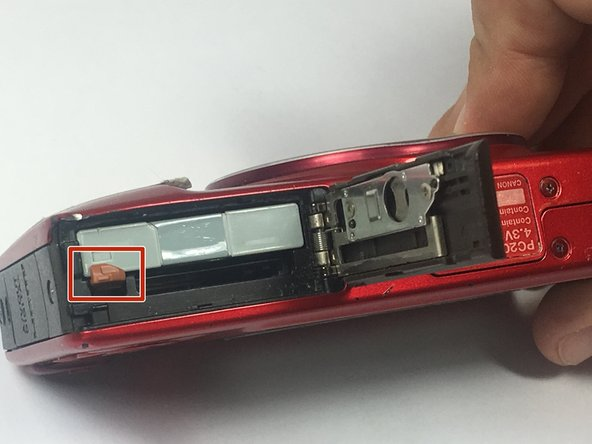 Depress the orange lever holding the battery in place to unlock it.
