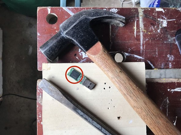 With the device on a firm surface, place the tip of the cold chisel across the middle of the memory chip and strike the cold chisel firmly with the hammer.