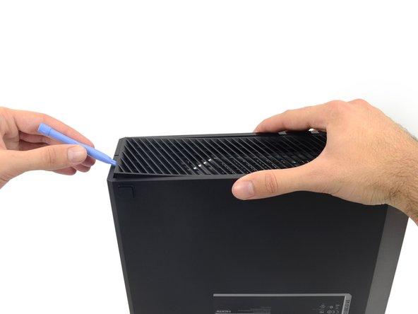 Usa uno strumento di apertura in plastica per sollevare e rimuovere la griglia di ventilazione che circonda la porta USB laterale.