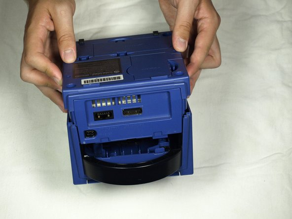 With the bottom side of the GameCube facing upward and the screws removed, carefully pull the outer shell of the unit away from the top half. Then place the inside of the unit facing up.