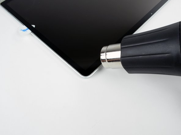 Use a heat gun to soften the adhesive under the display glass along the right and top edges of the display.