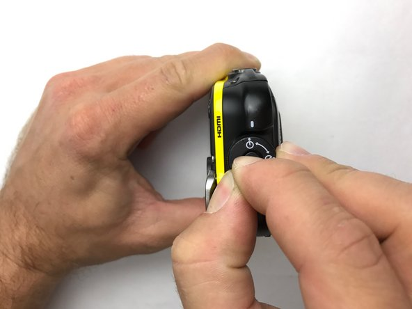Open the side panel which houses the battery compartment. Press the center button down and twist the dial.
