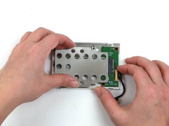 Use your hands to lift the metal bracket up and away from the SSD assembly.
