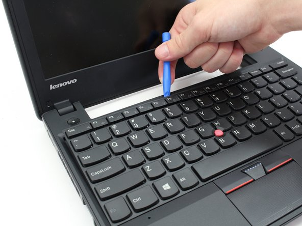 Using a small plastic opening tool, pry off the keyboard starting at a point closest to you and working around the perimeter.