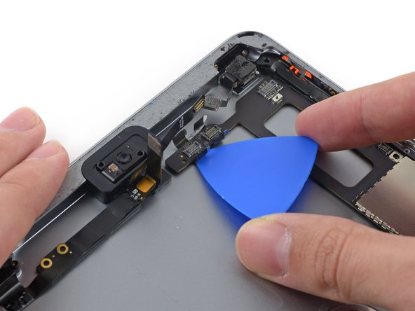 Carefully insert an opening pick under the logic board to the right of the front-facing camera.