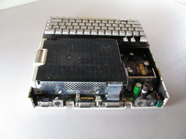Carefully detach ribbon connector from floppy disk drive by pulling it out horizontally.