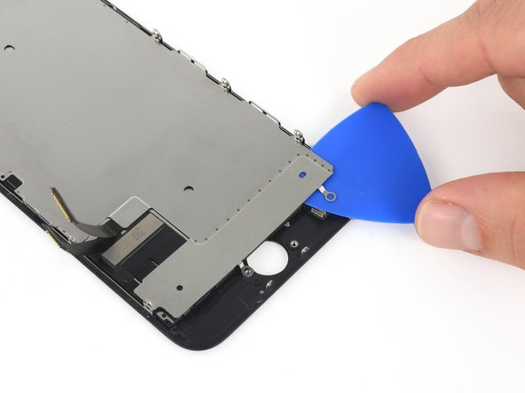 Use an opening pick to break up the adhesive near the home button  that holds the LCD shield plate to the display assembly.