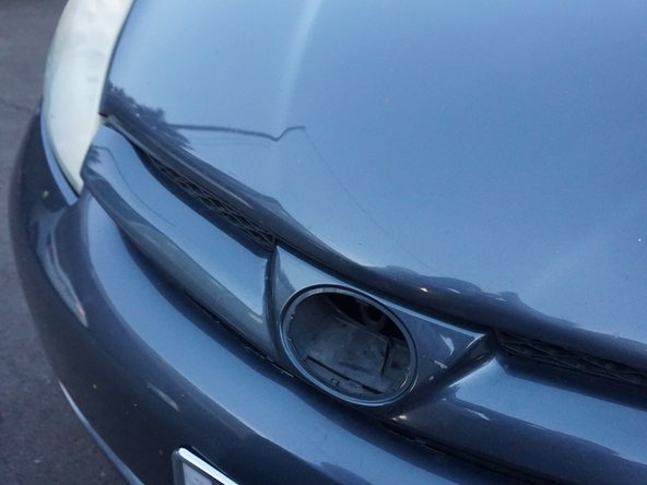 The notch for the emblem is located just below the car hood.