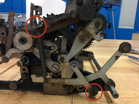 """On the right side rear, remove this screw, 3/16-32, threaded length 1/2"""", and the spring at the indicated point. There is nut on the other side, so it will be helpful to use a wrench to hold the nut."""