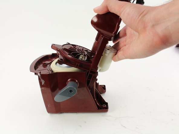 Pull up and back in a twisting motion to remove the motor from its casing.