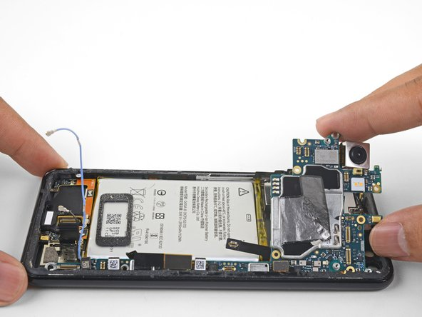 Carefully lift the top end of the motherboard away from the frame.