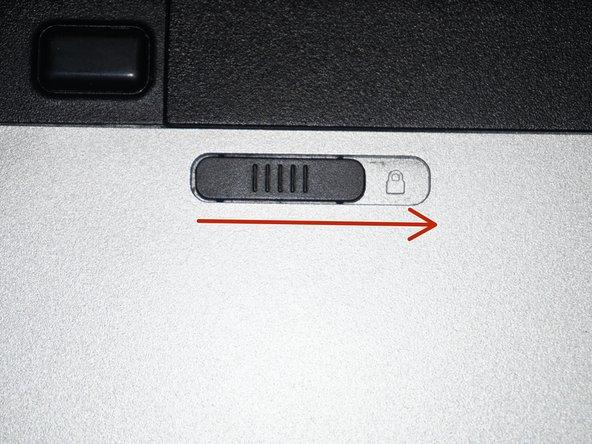 Une fois l'ordinateur éteint, enlevez la batterie. Glissez la languette de verrouillage sur la position déverrouillée (flèche rouge).
